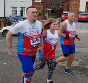 Jess running with two men in charity vests