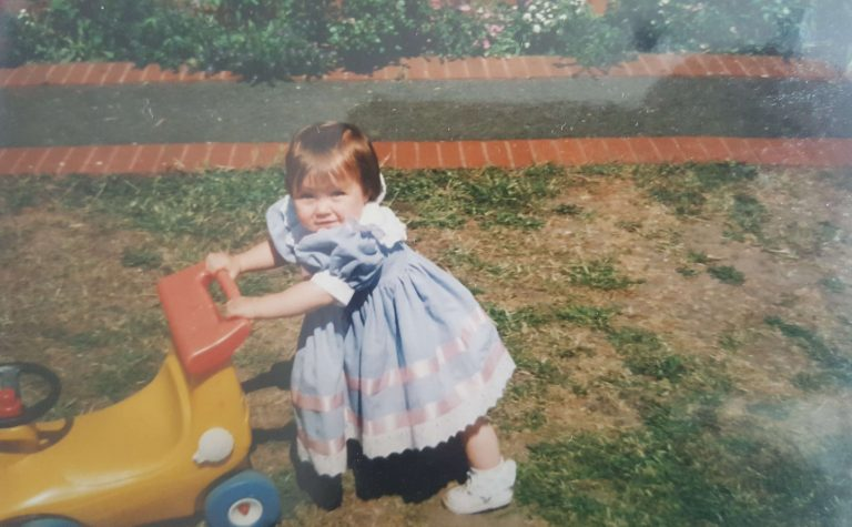 Lauren as a toddler hold a tric