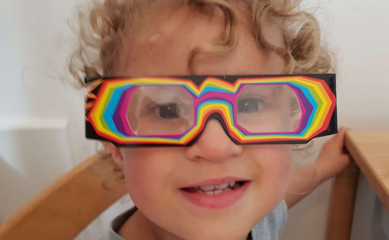 little girl looking at camera wearing 3d glasses at science party