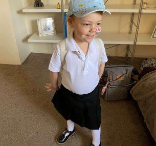 Isla in nursery uniform with cap